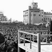 As he faces the Atomic Bomb Dome in Hiroshima, Emperor Hirohito waves his hat as he looks out over the crowd during a visit to the city on Dec. 7, 1947. | KYODO