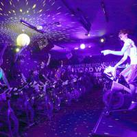 Stationary bikes are given a new spin in the light from a disco ball at a Feelcycle sports studio in Osaka on Feb. 22. | KYODO