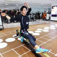 An instructor demonstrates the demanding exercise known as 'slacklining' at the Tip.X Tokyo Ikebukuro studio, in Toshima Ward, Tokyo, on July 24. | KYODO