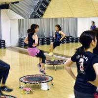 Gym-goers leap and twist on 'Ubound' trampolines at a Sports Club NAS Wakabadai studio in Inagi, western Tokyo, on July 22.   KYODO