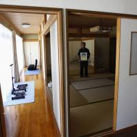 Mikio Watanabe holds a portrait of his late wife, Hamako, as he poses at his home at Yamakiya district in the town of Kawamata, Fukushima Prefecture, on June 23. The Fukushima District Court has ruled that Tokyo Electric was responsible for Hamako's suicide following the March 2011 triple core meltdown at the Fukushima No. 1 nuclear plant and must pay ¥49 million ($472,000) in compensation, Kyodo news reported. | REUTERS