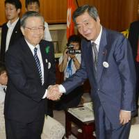 Newly appointed reconstruction minister Wataru Takeshita shakes hands with Fukushima Gov. Yuhei Sato after their meeting at the Fukushima Prefectural Government office on Thursday morning. | KYODO
