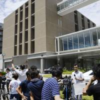 After learning that Yoshiki Sasai of the Riken Institute's Center for Developmental Biology had hanged himself, journalists flock to the building in Kobe on Aug. 5. | KYODO
