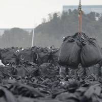 Bags full of contaminated waste are piled up Sept. 10 at a temporary storage site in Tomioka, Fukushima Prefecture, which has been evacuated since the nuclear crisis started in 2011. Buildings in the Fukushima No. 2 nuclear power plant can be seen beyond. | KYODO