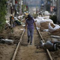 A local resident walks down tracks damaged by a landslide that swept through a residential area of Asaminami Ward in Hiroshima on Aug. 23. | REUTERS