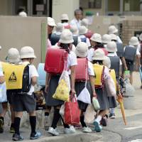 Children returning from summer vacation enter an elementary school Monday that was used to shelter people displaced by a mudslide that wrecked several homes in Asaminami Ward, Hiroshima, last month. | KYODO