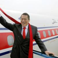 Diet lawmaker Antonio Inoki waves as he leaves Pyongyang international airport Tuesday after taking part in a rare two-day pro-wrestling event in North Korea. | KYODO