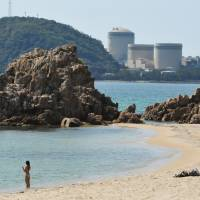 Kansai Electric Power Co. faces a tough decision on whether to decommission or apply to extend by two decades the operating lives of the aging No. 1 and No. 2 reactors (rear, from right) of the Mihama nuclear power plant in Fukui Prefecture. | KYODO