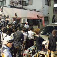 Journalists crowd a residential area in Nagata Ward, Kobe, where a bag containing what appeared to be the body of a girl was found Tuesday. | KYODO