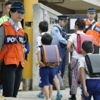 Police stand guard Wednesday at Nakura Elementary School, which Mirei Ikuta attended, in Kobe's Nagata Ward. | KYODO