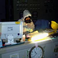 A photograph taken March 12, 2011, by an employee of Tokyo Electric Power Co. shows a fellow worker manning the control room for reactors 1 and 2 at the Fukushima No. 1 power plant. Working in the glow of a makeshift light, they were among the few employees who remained in the control room after a hydrogen explosion ripped through the building housing reactor 1. | KYODO