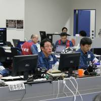 Naohiro Masuda (front row, second from left), head of Tokyo Electric Power Co.'s Fukushima No. 2 nuclear power plant, monitors the situation from the plant's emergency response office building in May 2011. | TEPCO/KYODO