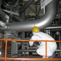 A Tokyo Electric Power Co. worker checks around a venting valve above the suppression chamber of reactor No. 5 at the Fukushima No. 1 power plant in December 2011. | TEPCO/KYODO