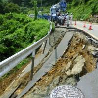 Workers in Ayabe City survey road damage that occurred due to heavy rains Thursday  in northern Kyoto. | KYODO