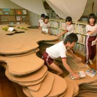 Pupils at Yoshima Daiichi Elementary School in Iwaki, Fukushima Prefecture, are encouraged to creep into the new cardboard cave in the library to enjoy reading books. | KYODO