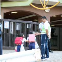A police officer stands guard at Nagura Elementary School in Nagata Ward, Kobe, on Tuesday. Mirei Ikuta, a first-grade student at the school, has been missing since Thursday.   KYODO