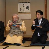 Indian Prime Minister Narendra Modi and Prime Minister Shinzo Abe eat cakes during a tea ceremony in Tokyo on Monday. | AFP-JIJI