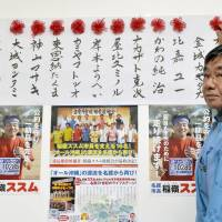 Nago Mayor Susumu Inamine places ribbons on the list of candidates who won Sunday's Nago Municipal Assembly election in Okinawa Prefecture in which anti-U.S. base candidates held onto a majority. | KYODO