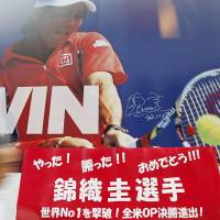 A poster featuring tennis player Kei Nishikori with a message celebrating his U.S. Open semifinal victory over Serbian player Novak Djokovic on Saturday adorns a sporting goods store in Tokyo on Monday. | REUTERS