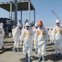 New industry minister Yuko Obuchi (third from right) walks inside the compound of the badly damaged Fukushima No. 1 nuclear power plant on Sunday as she inspects equipment installed to remove radioactive material from contaminated water. | KYODO