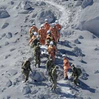 Firefighters and Self-Defense Forces troops carry a climber who became stranded near the top of Mount Ontake after it erupted on Saturday. More than 30 climbers are feared to have been killed in the volcanic explosion, according to some reports Sunday afternoon, although no official death toll has been issued yet. | KYODO