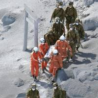 Firefighters and Self-Defense Forces troops on Sunday carry a climber who became stranded near the top of Mount Ontake after it erupted Saturday. More than 30 climbers are feared to have died in the volcanic explosion, police said Sunday afternoon, although an official toll had yet to be released. | KYODO