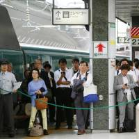 Passengers wait on a platform at Tokyo Station for bullet train service to resume on Wednesday. | KYODO
