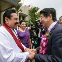 Sri Lankan President Mahinda Rajapakse shakes hands with Prime Minister Shinzo Abe in this handout photograph released by the Sri Lanka President's Office in Colombo on Sunday. | AFP-JIJI/SRI LANKA PRESIDENT'S OFFICE