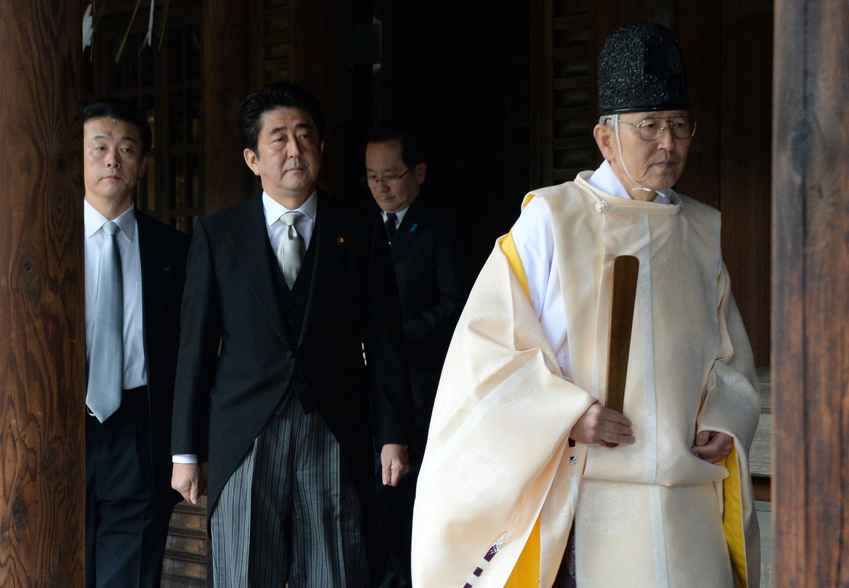 A Shinto priest leads Prime Minister Shinzo Abe during his visit to the controversial Yasukuni Shrine in Tokyo on Dec. 26 last year. | AFP-JIJI