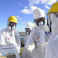 U.S. nuclear expert Lake Barrett (second from right) inspects the Fukushima No. 1 nuclear plant on Nov. 13 ahead of a hazardous operation to remove spent fuel rods from the storage pool atop reactor 4. Problems with radioactive water continue to plague efforts to clean up the site. | AFP-JIJI
