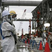 Utility staff work on the underground ice wall at the Fukushima No. 1 power plant in July. The ice wall hasn't been able to completely stop groundwater from mingling with radiation-tainted water in the reactor buildings. | REUTERS