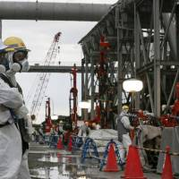 Workers conduct operations to construct an underground ice wall at Tokyo Electric Power Co.'s tsunami-crippled Fukushima No. 1 nuclear power plant in Fukushima Prefecture on July 9. | REUTERS