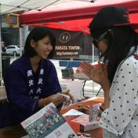 Sumika Ouchi, a senior at Tohoku University in Sendai, talks to a customer while selling camellia oil hand cream from Tohoku at the Japan Block Fair in New York on Saturday. | AYAKO MIE
