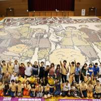 People pose Aug. 30 in in the village of Nakasatsunai, Hokkaido, in front of a 500-sq.-meter mosaic made from beans grown in the Tokachi region. | KYODO