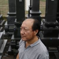 An Jianxing, a 50-year-old gravestone business owner and designer, stands in front of tombstones at his company showroom in Ibaraki Prefecture last Thursday. | REUTERS