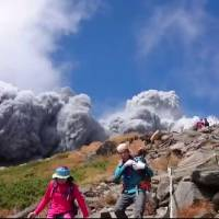 Hikers flee after Mount Ontake, a volcano straddling Nagano and Gifu prefectures, erupts on Saturday in this screen shot taken from YouTube. | YOUTUBE