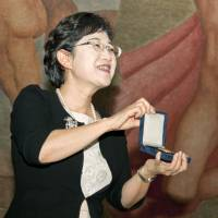 Children's book author Nahoko Uehashi accepts her gold medal in Mexico City on Wednesday after winning the 2014 Hans Christian Andersen Author Award. | KYODO
