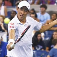 Kei Nishikori plays a shot from Canada's Milos Raonic in their fourth-round match at the U.S. Open on Monday. | REUTERS