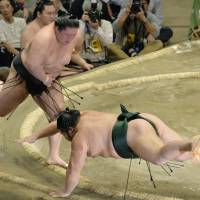 Working hard: Goeido earns a victory against Chiyotairyu on Thursday at the Autumn Grand Sumo Tournament.   KYODO