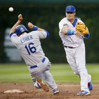 Look out: Chicago shortstop Javier Baez turns a double play over Los Angeles' Andre Either in the eighth inning on Saturday. | AP