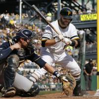 Not even close: Brewers catcher Jonathan Lucroy misses a wild pitch from Wily Peralta with the Pirates' Russell Martin at bat during the seventh inning on Sunday in Pittsburgh. The Pirates won 1-0. | AP