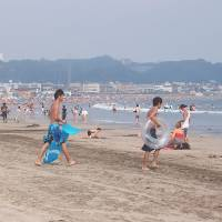 Hot mess: People crowd a beach in Kamakura, Kanagawa Prefecture. Is summer's traditional association with relaxation becoming a distant memory in Japan? | 'BEACH @ HASE @ KAMAKURA' BY GUILHEM VELLUT; USED UNDER CC BY 2.0