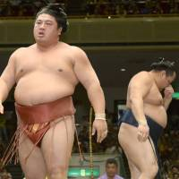 Mission accomplished: Yoshikaze (left) leaves the ring after beating Kakuryu at the Autumn Grand Sumo Tournament on Monday. | KYODO