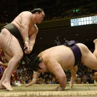 Another one bites the dust: Hakuho throws Takekaze to the ground at the Autumn Grand Sumo Tournament on Wednesday. | KYODO