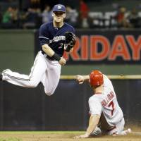 Hang time: Milwaukee's Scooter Gennett watches his throw to first to complete a double play against St. Louis in the fifth inning on Thursday. The Cardinals edged the Brewers 3-2. | AP