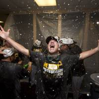 Raise the Jolly Roger: The Pirates celebrate after qualifying for the postseason with a win over the Braves on Tuesday. | AP