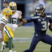 Stay away: Seattle QB Russell Wilson straight-arms Green Bay's Ha Ha Clinton-Dix in the season opener on Thursday night.   AP