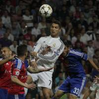 Seeing stars: Real Madrid's Cristiano Ronaldo heads the ball during a 5-1 win over Basel on Tuesday. | AP