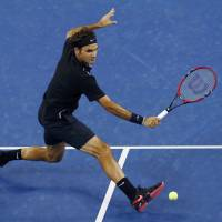 Big comeback: Roger Federer plays a shot from France's Gael Monfils in their quarterfinal match at the U.S. Open on Thursday. Federer won 4-6, 3-6, 6-4, 7-5, 6-2. | REUTERS