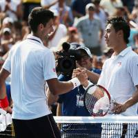 Kei Nishikori is congratulated by Novak Djokovic following their semifinal match at the U.S. Open in New York on Saturday. | AP